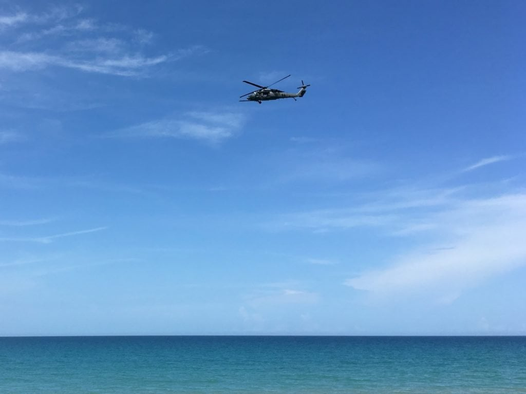 Another helicopter flying low over the beach