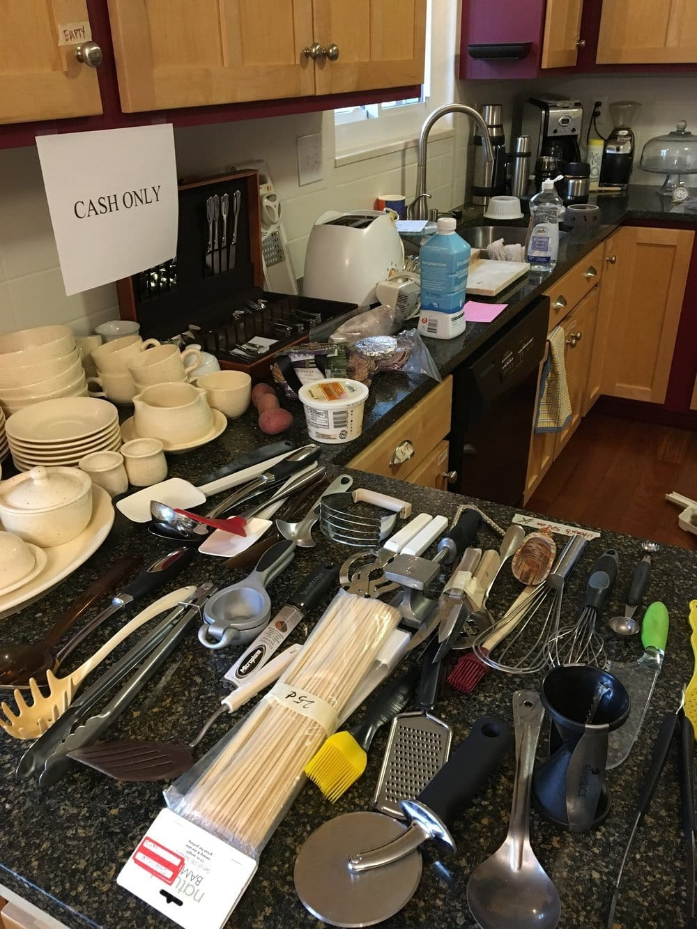 Kitchen with counters covered in utensils and dishes for sale