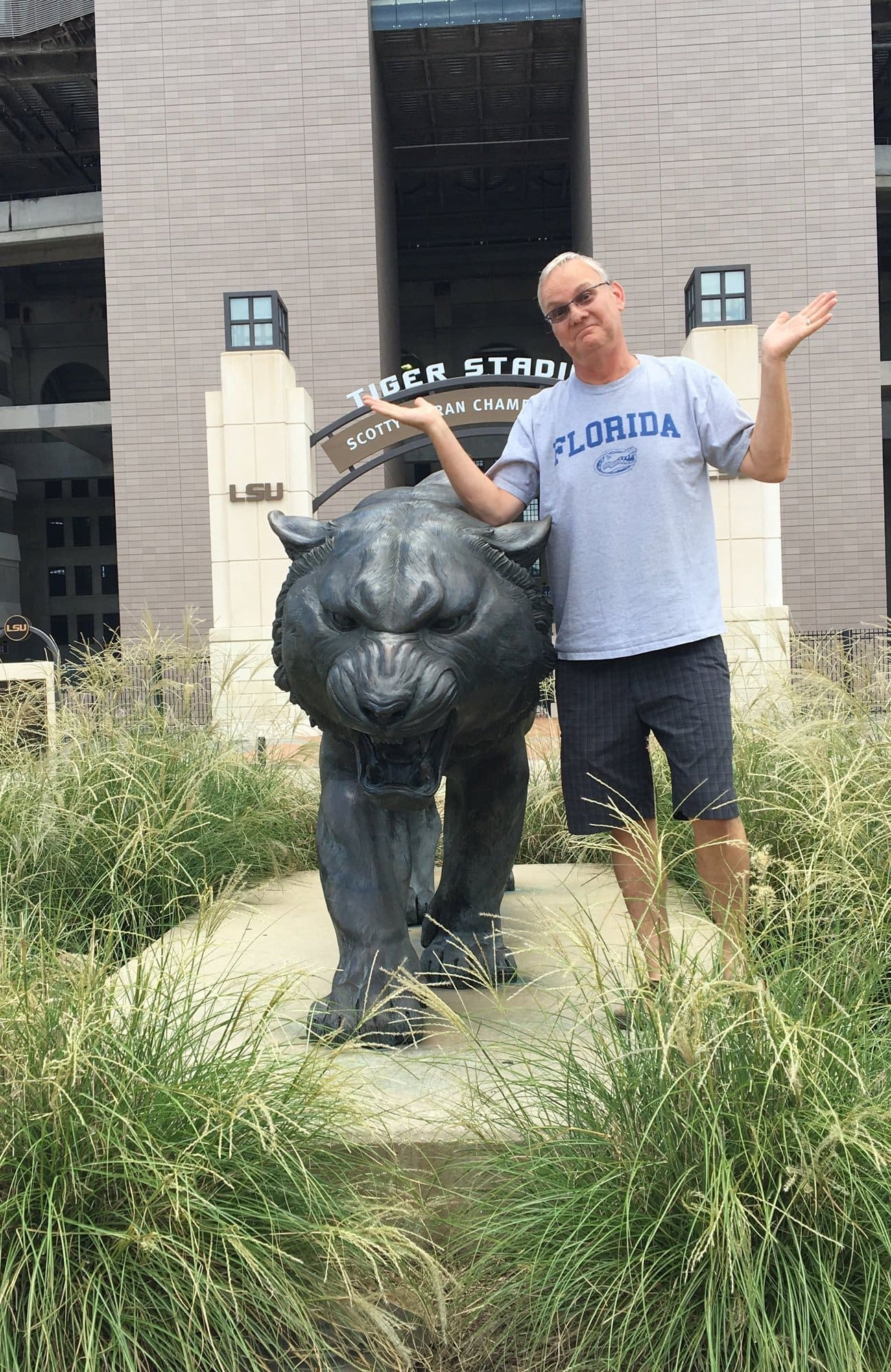 Norm with LSU Tiger statue, wearing a Florida Gators t-shirt