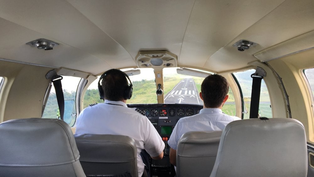 View over the shoulder of the pilot and copilot of small plane
