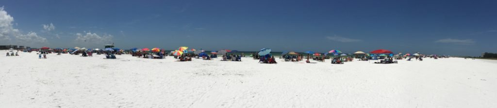 Long white beach full of umbrellas and chairs