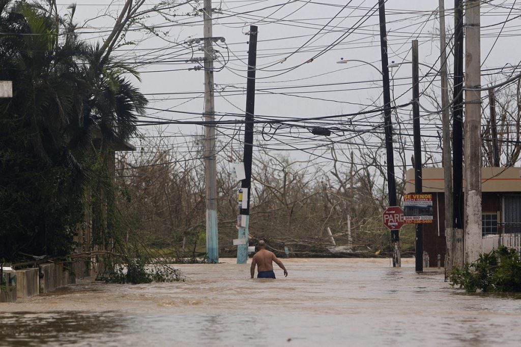 Man wading down a street in waist-deep water